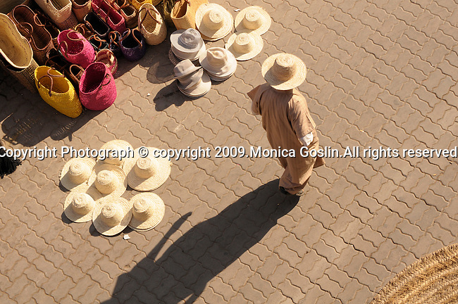 A man walks through the market in Marrakesh, Morocco and passes vendors selling straw hats, baskets and more..