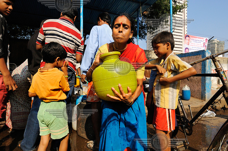 Slum dwellers collecting water from a public supply point in Cuffe Parade district in South Mumbai, which is also home to some of the city's most exclusive residential blocks.