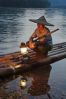 Traditional fisherman with lantern at sunset, Li River, near Guilin, China