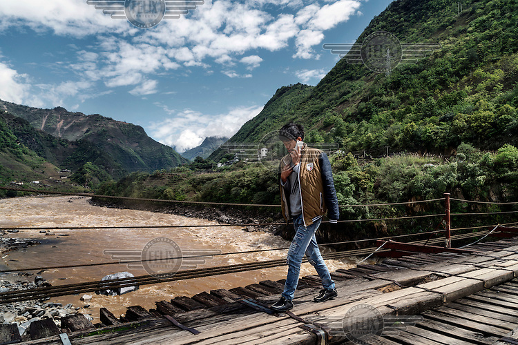 A youth speaks on a mobile phone while walking across the suspension bridge spanning the Nujiang River in Mian Gu village.