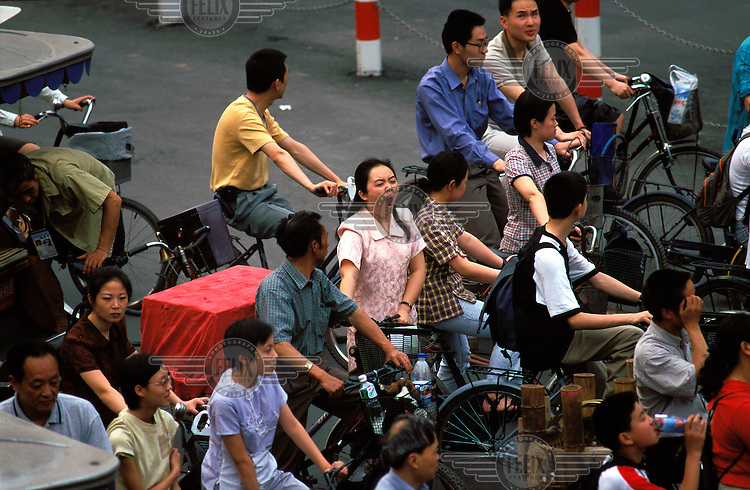 ©Mark Henley/Panos Pictures..China, Sichuan, Chengdu..Tired woman yawning while wating at traffic light with her bicycle during rush hour.