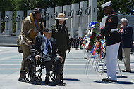 Washington, DC - June 6, 2014: WWII veteran Henry Mendoza (seated) is escorted by John McCaskill (left), of the Nation Park Service, during a wreath laying ceremony at the National World War II Memorial. The ceremony was part the 70th anniversary of the D-Day invasion honoring WWII veterans. Mendoza was a member of the 9th Air Force in the months leading up to Operation Overlord. (Photo by Don Baxter/Media Images International)
