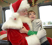 NWA Democrat-Gazette/ANDY SHUPE<br /> Santa Claus gets a hug Saturday, Dec. 1, 2018, from Austin Holliman-Shaver, 5, of Decatur during the annual Christmas Train at the Arkansas &amp; Missouri Railroad in Springdale. The event features a 40-minute ride to Johnson and back aboard a 1940s-era passenger car with Christmas carols. Santa Claus sat for photographs with families in a caboose while games and pony rides were available at the depot.