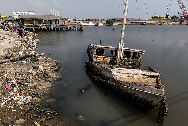 13 August 2019, Jakarta, Indonesia: A boat sits rotting in the sea just over the sea wall from the residential area of Waduk Pluit. The local residents were speaking about the lack of water facilities that the local poor population has access to. Water is hauled in each day by motorcycle and trucks and by hand to allow residents of the kampungs to  buy it for washing and to do laundry. Separate water is needed for drinking. The Jakarta Governor is proposing a program to send in trucks of water for the locals to get for free. They are living in villages below the seawater line on the coast of Jakarta that is sinking faster than anywhere else in the world so they have the position of being surrounded by water yet not having access to clean supplies. Picture by Graham Crouch/The Australian