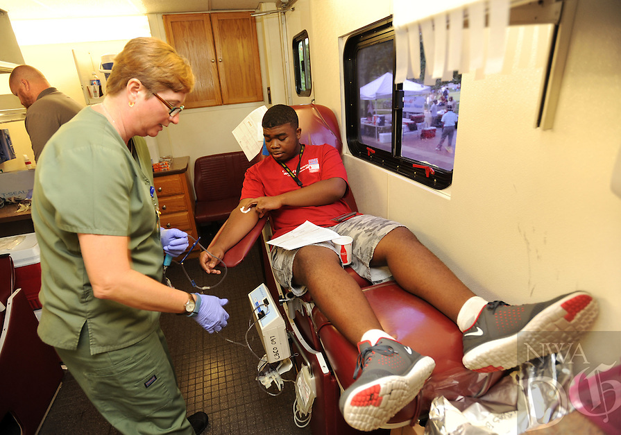 NWA Democrat-Gazette/ANDY SHUPE<br /> Montrell Plummer, (right) a freshman at the University of Arkansas from Little Rock, is assisted Wednesday, Sept. 9, 2015, by Rebecca Long, a donor specialist for the Community Blood Center of the Ozarks, while donating blood during the annual Muslims for Life blood drive sponsored by Al-Islam Students Association at the University of Arkansas in Fayetteville. The event marks the 14th anniversary of the 9/11 terrorist attacks and had the goal of collecting 200 pints of blood from the campus community.