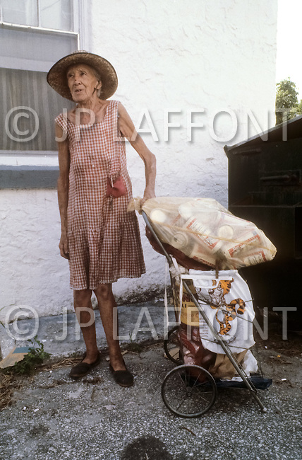Miami Beach, Florida, U.S.A, September, 1980. America severely marked by the recession. This elderly woman, a widow without any income, is looking in the garbage cans for used cans in order to sell them  to a recycling factory. She works everyday for a couple of dollars.