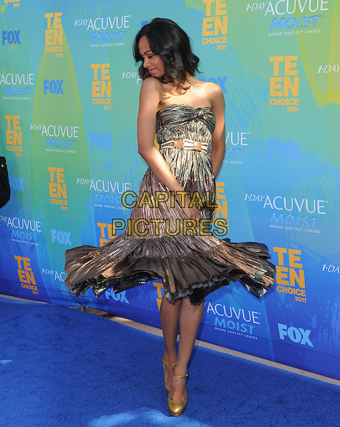 Zoe Saldana.The Fox 2011 Teen Choice Awards held at Gibson Ampitheatre in Universal City, California, USA..August 7th, 2010                    .full length strapless gold knot knotted strapless spin spinning twirling looking down profile dress .CAP/RKE/DVS.©DVS/RockinExposures/Capital Pictures.