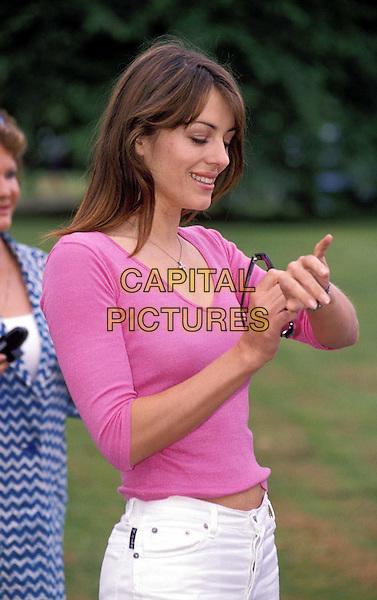LIZ HURLEY.Ref:8687 .pink v-neck jumper, cross crucifix necklace, watch, checking time, hands, half length, half-length.www.capitalpictures.com.sales@capitalpictures.com.© Capital Pictures