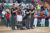 Erie SeaWolves catcher Austin Green (7) during the nation anthem with umpires Sean Ryan, Randy Rosenberg, and Chris Graham before a game against the Richmond Flying Squirrels on May 27, 2016 at Jerry Uht Park in Erie, Pennsylvania.  Richmond defeated Erie 7-6.  (Mike Janes/Four Seam Images)