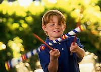 Boy playing with rhythm sticks.