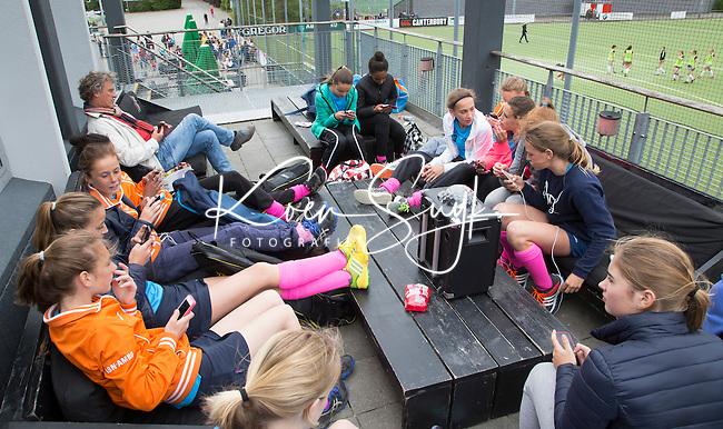 AMSTELVEEN - NK Schoolhockey. relaxen tussen de wedstrijden door met de mobieltjes.   © 2015 Koen Suyk