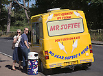 People buying ice cream from Mr Softee van at Mistley Walls, Essex, England
