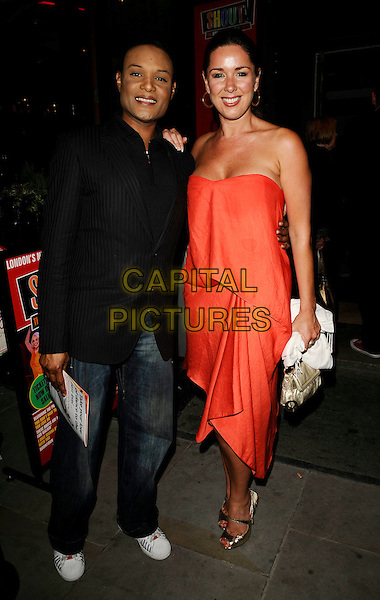 "STEDMAN PEARSON (FIVE STAR) & CLAIRE SWEENEY.The ""Shout!"" press night, the Arts theatre, London, England..April 29th, 2009.full length black jacket jeans denim 5 red orange strapless dress gold peep toe strap mary janes shoes clare sweeny .CAP/CAN.©Can Nguyen/Capital Pictures."