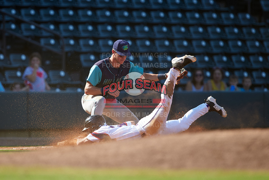 JJ Muno (10) of the Winston-Salem Rayados slides head first into third base as Nolan Jones (10) of the Lynchburg Hillcats fields a throw at BB&T Ballpark on June 23, 2019 in Winston-Salem, North Carolina. The Hillcats defeated the Rayados 12-9 in 11 innings. (Brian Westerholt/Four Seam Images)