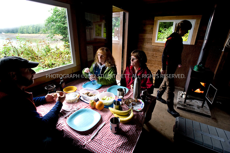 9/18/2008--Petersburg, Alaska, USA..From left to right: Scott Roberge, Shannon Peeler, Anne Volk and Tracey Kelly eating lunch in the Cascade Creek cabin in the Tongass National Forest. Reached in about 1 hour from nearby Petersburg, the cabin offers visitors easier access to the Alaskan wilderness without having to camp...Petersburg is on the north end of Mitkof Island, near the Tongass National Forest. A major fishing port, the town of 3500 is also a good jumping off point to see the Alaskan wilderness in south eastern Alaska. Petersburg can be reached on Alaskan Airlines via Seattle or nearby Juneau to the north...©2008 Stuart Isett. All rights reserved.