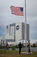 American flag flies above NASA's Vehicle Assembly Building, the fourth largest building in the world, the morning of Endeavour's scrubbed launch about 3 1/2 hours before the 3:47 scheduled liftoff due to mechanical woes at Kennedy Space Center, Cape Canaveral, Florida, USA, April 29, 2011. Photo by Debi Pittman Wilkey