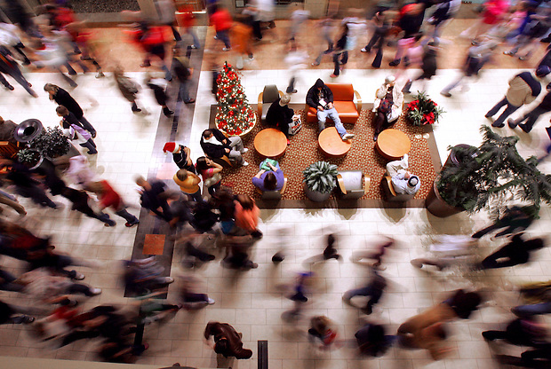 A whirlwind of shoppers moves through Jordan Creek Town Center while some sit to take a break in the early morning hours on black Friday.