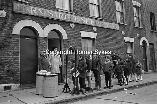 Farthing Bundles. Fern Street Settlement, east London. England 1971. Florrie Ally standing in the doorway.