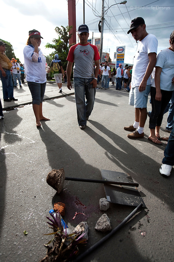 5 July 2009 - Tegucigalpa, Honduras  A makeshift memorial to a supporter killed by army gub fire. Supporters of ousted Honduras' President Manuel Zelaya holds bullets shot by soldiers at the protesters at the international airport in Tegucigalpa. At least one person was killed and ten were badly wounded when protesters demanding the return of ousted Honduran President Manuel Zelaya clashed with troops at the Tegucigalpa airport. Zelaya turned back from an attempted return home on Sunday after soldiers clashed with his supporters as he tried to land, fueling tensions over the coup that toppled him. Photo credit: Benedicte Desrus