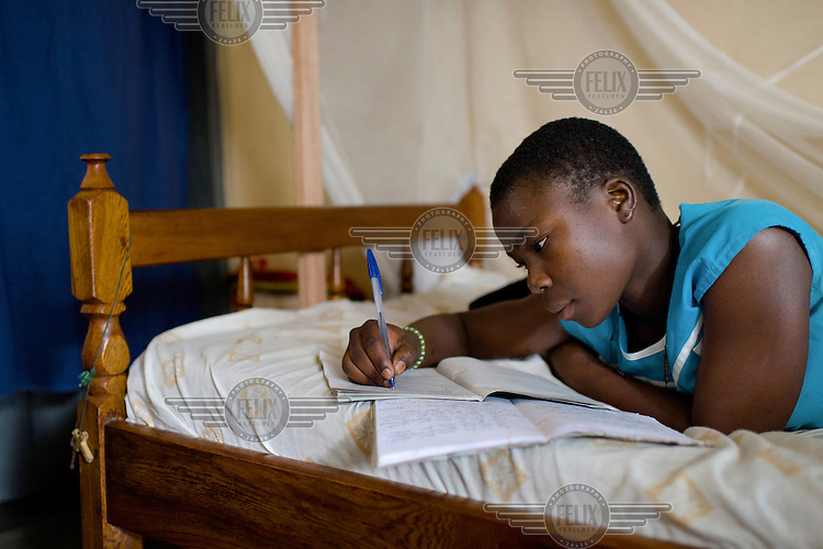 Peninah Mamayi, the Health Prefect at Achilet Primary School, revising for exams at her home. As Health Prefect she educates her peers on a range of health and hygiene issues, including menstrual hygiene. She says: 'I wanted to be a health prefect so I could help my friends be clean. I teach them about cleaning their latrines at home, keeping their compounds clean at home, cutting their hair and fingernails, washing their clothes. I tell them that after they pick rubbish they should wash their hands. I tell them to be bathing daily so that they don't smell. And to wash their Afripads very well, and to dry them very well.' An Afripads user herself, she says Afripads (locally manufactured reusable sanitary pads) 'have improved my life because they don't disturb me, and I can just sit and be comfortable. Even if I play or I jump, nothing happens.'