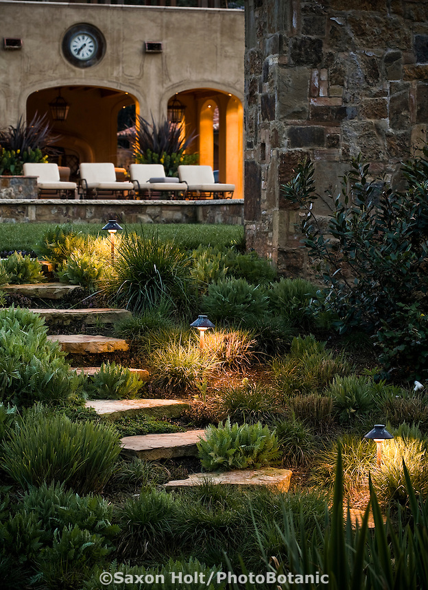 California home with pathway and pale stone steps with night lighting leading to outdoor living patio with chairs