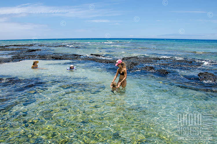 Two mothers and their children play in tide pools at a beach in Puako, South Kohala, Big Island of Hawai'i.