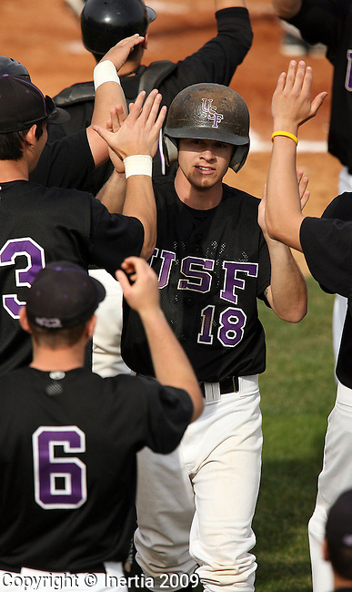 SIOUX FALLS, SD - APRIL 17:  Cody Minich #18 of the University of Sioux Falls is congratulated by teammates after scoring a run against Morningside during the second game of their doubleheader Friday afternoon at the Sioux Falls Stadium. (Photo by Dave Eggen/Inertia)