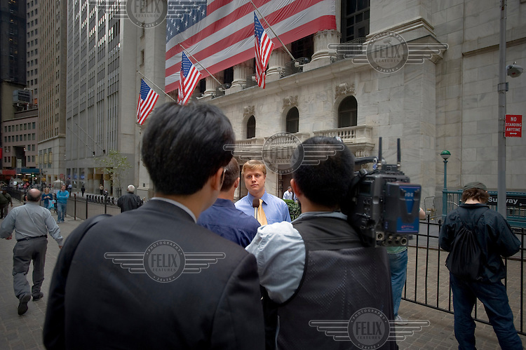 A Wall Street banker is interviewed outside the New York Stock Exchange (NYSE) on the day when share prices plummeted after the US Government failed to reach an agreement to bail out the country's ailing financial institutions.