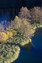 Upper Lakes surrounded by autumnal woodland, Plitvice Lakes National Park, Croatia. November.