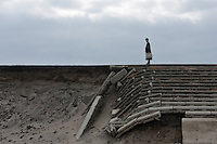 A man stands on the damaged coastal wall and tsunami defenses in Shimo Masuda near Sendai airport. Miyagi, Japan. Wednesday, May 4th 2011. Residents had 30 minutes to flee the tsunami after a magnitude 9 earthquake struck off the coast on March 11th leveling the town and killing large numbers of people.
