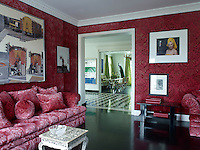 The walls and sofas in the living room are covered in matching red brocade velvet designed by Sabina Fay Braxton