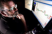 Andy Shaffer monitors daily stock market trends while working from his Des Moines home.  He recently left his job as an IT specialist for Principal Financial to work on his own from home.