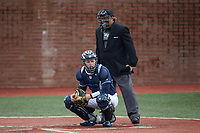 Wingate Bulldogs catcher Logan McNeely (18) looks to the dugout for the pitch call as the home plate umpire looks on during the game against the Concord Mountain Lions at Ron Christopher Stadium on February 1, 2020 in Wingate, North Carolina. The Bulldogs defeated the Mountain Lions 8-0 in game one of a doubleheader. (Brian Westerholt/Four Seam Images)