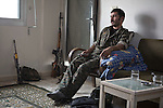 28/09/2014. Al-Yarubiyah, Syria. A Syrian-Kurdish YPG fighter watches television in the Syrian town of Al-Yarubiyah.<br /> <br /> Facing each other across the Iraq-Syria border, the towns of Al-Yarubiyah, Syria, and Rabia, Iraq, were taken by Islamic State insurgents in August 2014. Since then The town of Al-Yarubiyah and parts of Rabia have been re-taken by fighters from the Syrian Kurdish YPG. At present the situation in the towns is static, but with large exchanges of sniper and heavy machine gun fire as well as mortars and rocket propelled grenades, recently occasional close quarter fighting has taken place as either side tests the defences of the other.