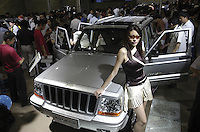 A model poses beside a Beijing jeep's Chrysler Jeep 2500 at the Auto China 2004 exhibition in Beijing, China..