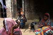 21 year old Seema Devi (left) sits with her sister-in-law (right) while Seema's husband, Vinay Paswan takes care of their 9 month old daughter, Vaishnavi Kumari in their kitchen of their hut in Shivpur Hariyya village in Raxaul district of Bihar.
