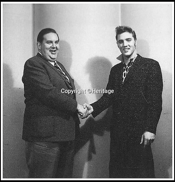 BNPS.co.uk (01202 558833)<br /> Pic: Heritage/BNPS<br /> <br /> ***Please Use Full Byline***<br /> <br /> Elvis with RCA executive Steve Sholes, at the time of the signing.<br /> <br /> The outfit Elvis Presley was wearing when he signed the momentous recording contract that rocketed him to international stardom has emerged for sale for 24,000 pounds.<br /> <br /> Despite being just 20 when he put pen to paper, Elvis was already the hottest thing in country music and was snapped up by record label giant RCA for a whopping 40,000 dollars - the equivalent of almost 400,000 dollars or 237,000 pounds today.