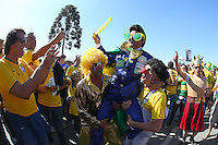 A Brazilian fan in fancy dress is the centre of attention as fans soaks up the atmosphere outside the Itaquerao stadium ahead of kick off in the opening match of the 2014 World Cup between Brazil and Croatia