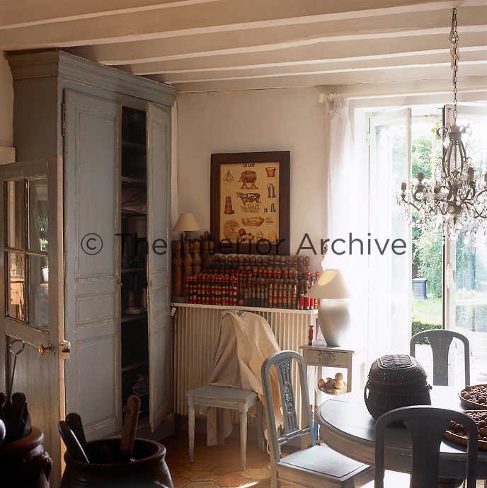 A detail of a rustic dining room with French country style furniture. A chandelier hangs above a blue painted table and chairs. French doors lead to the garden.