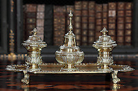 Silver tray with ink pot, pen holder and bell, on a table inlaid with Jacaranda wood and wood from Sri Lanka, in the Black Room of the Joanina Library, or Biblioteca Joanina, a Baroque library built 1717-28 by Gaspar Ferreira, part of the University of Coimbra General Library, in Coimbra, Portugal. The bookshelves were made, gilded and lacquered by Manuel da Silva. The Casa da Livraria was built during the reign of King John V or Joao V, and consists of the Green Room, Red Room and Black Room, with 250,000 books dating from the 16th - 18th centuries. The library is part of the Faculty of Law and the University is housed in the buildings of the Royal Palace of Coimbra. The building is classified as a national monument and UNESCO World Heritage Site. Picture by Manuel Cohen