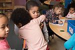 Education Preschool 3-4 year olds girl showing sympathy for sad boy, giving him a hug