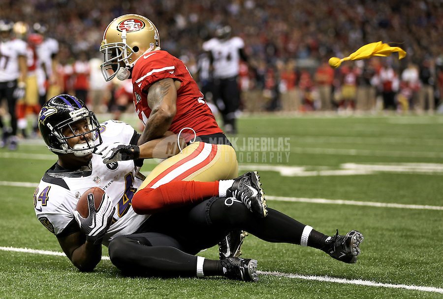 Feb 3, 2013; New Orleans, LA, USA; A penalty flag for face masking flies as Baltimore Ravens tight end Ed Dickson (84) is tackled by San Francisco 49ers strong safety Donte Whitner (31) in the second quarter in Super Bowl XLVII at the Mercedes-Benz Superdome. Mandatory Credit: Mark J. Rebilas-