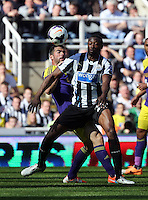 Pictured: Jordi Amat of Swansea (L) challenged for a header by Shola Ameobi of Newcastle. Saturday 19 April 2014<br />
