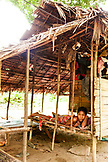 PHILIPPINES, Palawan, Barangay region, young Batak woman rests in her home in Kalakwasan Village