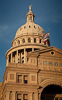 Texas Flag flies atop the Texas State Capitol and dome in downtown Austin, Texas.
