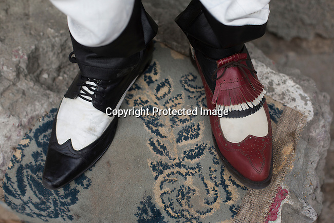 "KINSHASA, DEMOCRATIC REPUBLIC OF CONGO - FEBRUARY 13: A Sapeur from the group belonging to Papa Griffe shows off different shoes on February 13, 2016 in Kinshasa, DRC. The word Sapeur comes from SAPE, a French acronym for Société des Ambianceurs et Persons Élégants. or Society of Revellers and Elegant People. and it also means, .to dress with elegance and style"". Most of the young Sapeurs are unemployed, poor and live in harsh conditions in Kinshasa, a city of about 10 million people. For many of them being a Sapeur means they can escape their daily struggles and dress like fashionable Europeans. Many hustle to build up their expensive collections. Most Sapeurs could never afford to visit Paris, and usually relatives send or bring clothes back to Kinshasa. (Photo by Per-Anders Pettersson)"