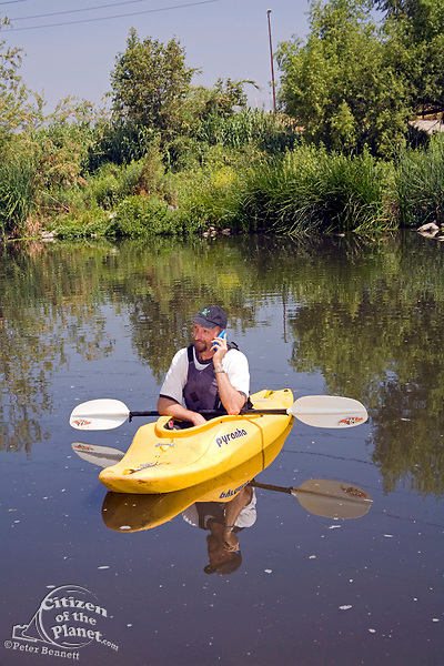 Kayaker George Wolfe of the LaLa Times on a cell phone. FoLAR' (Friends of the LA River) annual river cleanup, La Gran Limpieza, was held  May 9, 2009. Thousands of volunteers at 14 sites pulled out accumlated trash, mostly plastic bags, from river runoff that might normally find it's way downstream into the Pacific Ocean.