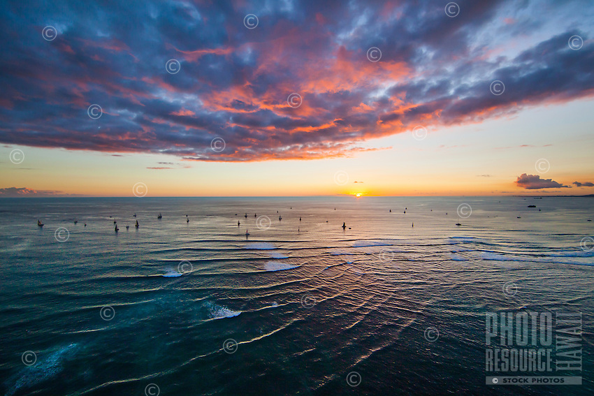 An ultra-wide shot of a colorful sunset in Waikiki, O'ahu, with sailboats dotting the horizon beneath red and blue clouds.