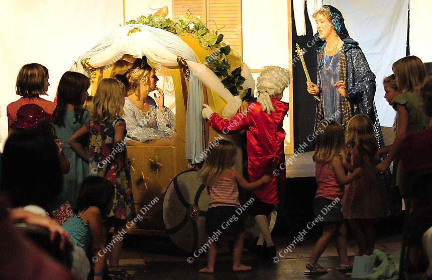 Cinderella (Ashleigh C.J. Nelson) gets into her magic carriage as her Fairy Godmother (Anne Johnson) and children in the audience look on.