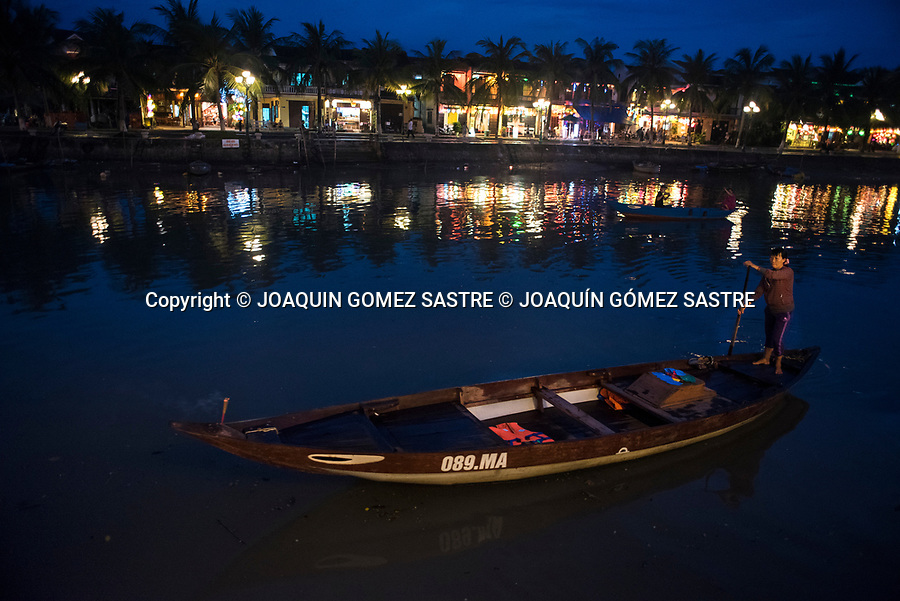 A woman sails along the Thu Bon River in the small coastal city of Hoi An (Vietnam)